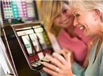 View larger image of Two ladies enjoying their time at the slot machines at THE RV PARK AT ROLLING HILLS CASINO AND RESORT image #6