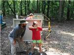 View larger image of Girl shooting bow at QUAIL CREEK RV RESORT image #7