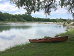 View larger image of Canoe on the shore of the lake at ABOVE AND BEYOND RIVER RESORT RV PARK image #4