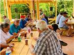 View larger image of A group of people eating at picnic tables at THE HEMLOCKS RV AND LODGING image #6