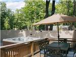 View larger image of Hot tub alongside cabin patio  at WESTWARD SHORES COTTAGES  RV RESORT image #9