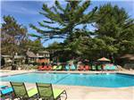 View larger image of Swimming pool with colorful chaise lounges at SANDY PINES CAMPGROUND image #1