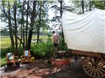 View larger image of Man exiting a covered wagon at SANDY PINES CAMPGROUND image #6