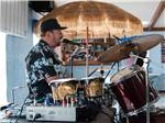View larger image of A man in a hat playing drums at BLUEBONNET RV RESORT image #3