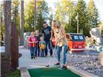 View larger image of A family eating at a picnic table at WEST GLACIER RV PARK  CABINS image #3
