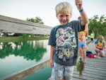 View larger image of Boy showing off fish at SPLASHWAY WATERPARK  CAMPGROUND image #6