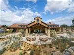 View larger image of Large wooden clubhouse with patio furniture out front at CAVA ROBLES RV RESORT image #1