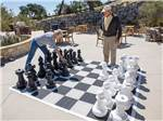 View larger image of Couple playing chess on enormous outdoor chess board at CAVA ROBLES RV RESORT image #5