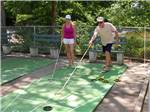 View larger image of Couple playing shuffleboard at SCENIC RV RESORT image #6