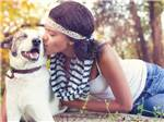 View larger image of Young woman in white tank top and blue jeans kissing small dog at CAROLINA PINES RV RESORT image #5