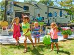 View larger image of Young children in bright colored clothing playing with RV in background at OUTER BANKS WEST KOA image #2