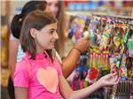 View larger image of Young girl in pink shirt looking at toys hanging in a convenience store at OUTER BANKS WEST KOA image #7