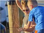 View larger image of Mother holding up a fishing net with her son on a dock at OUTER BANKS WEST KOA image #8