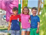 View larger image of Two young boys and one young girl in brightly colored clothing at playground at OUTER BANKS WEST KOA image #9