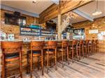 View larger image of Modern bar with stained wood walls and hardwood floor at BLUE WATER RV RESORT image #4