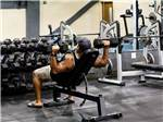 View larger image of A strong man lifting dumbbells on his back at THE RIDGE OUTDOOR RESORT image #4