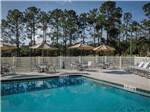 View larger image of The pool area with lounge chairs and tables with umbrellas at RIDGECREST RV RESORT image #1
