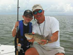 View larger image of Man and a young boy holding a caught fish  at PRESERVATION POINT RV RESORT image #5