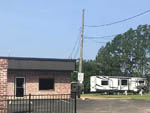 View larger image of Trailer parked near brick office building at EASTERN PINES RV PARK image #1