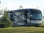 View larger image of Big rig parked in a grassy site at KASOTA RV RESORT image #1