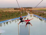 View larger image of Two people on zip lines over water at KASOTA RV RESORT image #3