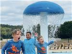 View larger image of A Native American talking to two children in front of a teepee at DINOSAUR VALLEY RV PARK image #3