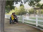View larger image of A couple sitting on a bench under a tree at PECHANGA RV RESORT image #10