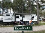 View larger image of Parked trailer with couple and sign reading Recreation Ln at LAKE CITY RV RESORT image #6