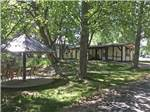 View larger image of Covered seating area among the trees at UNCOMPAHGRE RIVER ADULT RV PARK image #6