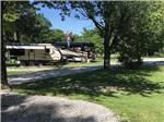 View larger image of Trailer and big rig parked in site with trees at SINGING HILLS RV PARK image #6