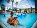 View larger image of Man with child in indoor pool at LAZYDAYS RV RESORT image #3