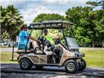 View larger image of Couple riding in golf cart at WEKIVA FALLS RV RESORT image #5