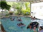 View larger image of A bunch of kids playing in an indoor pool at PECAN PARK RIVERSIDE RV PARK image #5
