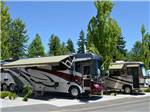 View larger image of Two large RVs parked at MAPLE GROVE RV RESORT image #7