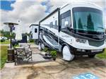 View larger image of Large white and gray RV with tires covered parked alongside patio at PECAN PARK RV RESORT image #4