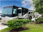View larger image of Large RV unit with slideout parked alongside green landscaping at PECAN PARK RV RESORT image #5