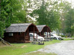 View larger image of Log cabins side by side with vehicles parked alongside them at BRUNSWICK BEACHES CAMPING RESORT image #4