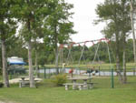 View larger image of Swing set with green fence around it and picnic tables in the foreground at BRUNSWICK BEACHES CAMPING RESORT image #8