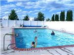View larger image of Splashing in the pool with white fence surrounding it at HORN RAPIDS RV RESORT image #11