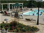 View larger image of Swimming pool with outdoor seating at TRAVERSE BAY RV RESORT image #6