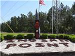View larger image of Indian statue next to rock sign at entrance at INDIAN POINT RV RESORT image #1