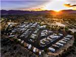 View larger image of Aerial view over RV campground and mountains at sunset at DISTANT DRUMS RV RESORT image #1