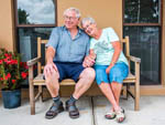 View larger image of An elderly couple holding hands and sitting on a bench at HILLCREST RV RESORT image #5