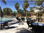 View larger image of Tables and chairs next to the pool at NEVADA TREASURE RV RESORT image #2