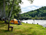 View larger image of Man sitting next to his tent on the river bank at HOQUIAM RIVER RV PARK image #8