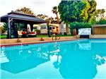 View larger image of Swimming pool with covered seating area at SHADOW HILLS RV RESORT image #1