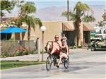 View larger image of Couple on a tandem bike at SHADOW HILLS RV RESORT image #5