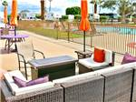 View larger image of Seating area by pool with row of RVs at SHADOW HILLS RV RESORT image #9