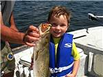 View larger image of Boy showing off fish at TAMPA SOUTH RV RESORT image #10