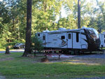 View larger image of RV trailer at a grassy tree-lined site at DEER RUN CAMPING RESORT image #5